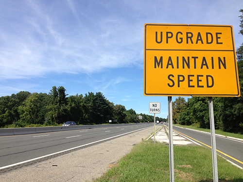 "Picture of a sign reading ""Upgrade. Maintain speed."" Next to a highway."